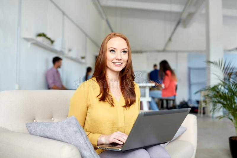 Gelukkige vrouw met laptop die op kantoor werken stock fotografie