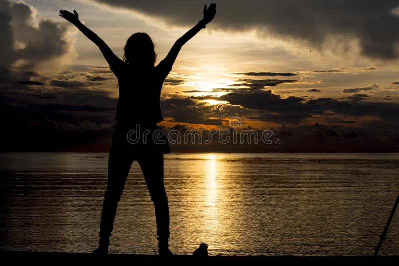 Gelukkige vrouw met ochtendzon bij het strand royalty-vrije stock afbeelding