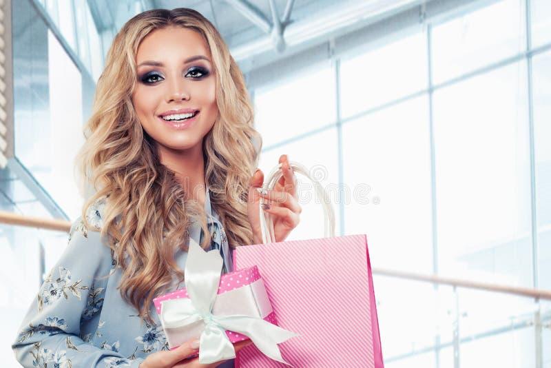 Gelukkige vrouw met roze gift Vrolijk meisje in bureau stock foto