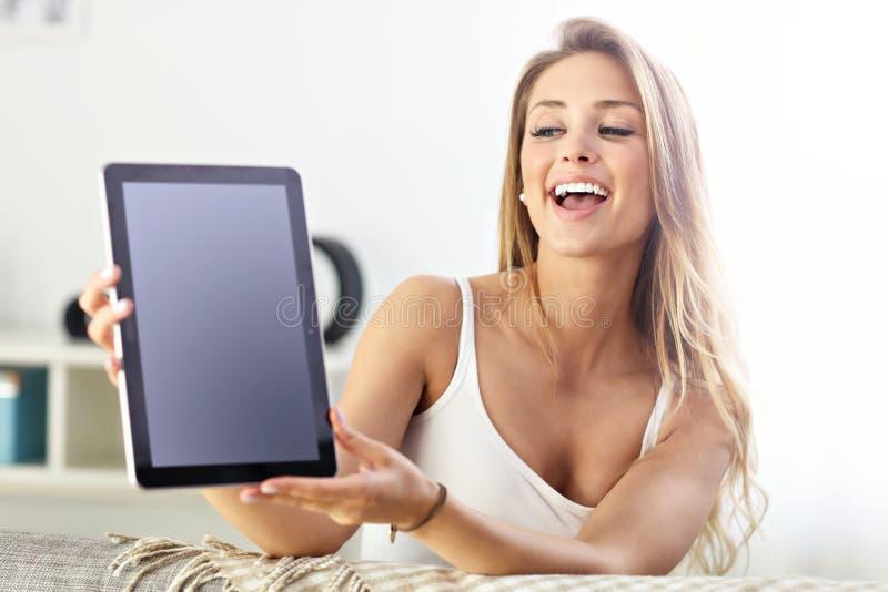 Gelukkige vrouw met tablet op bank stock afbeeldingen