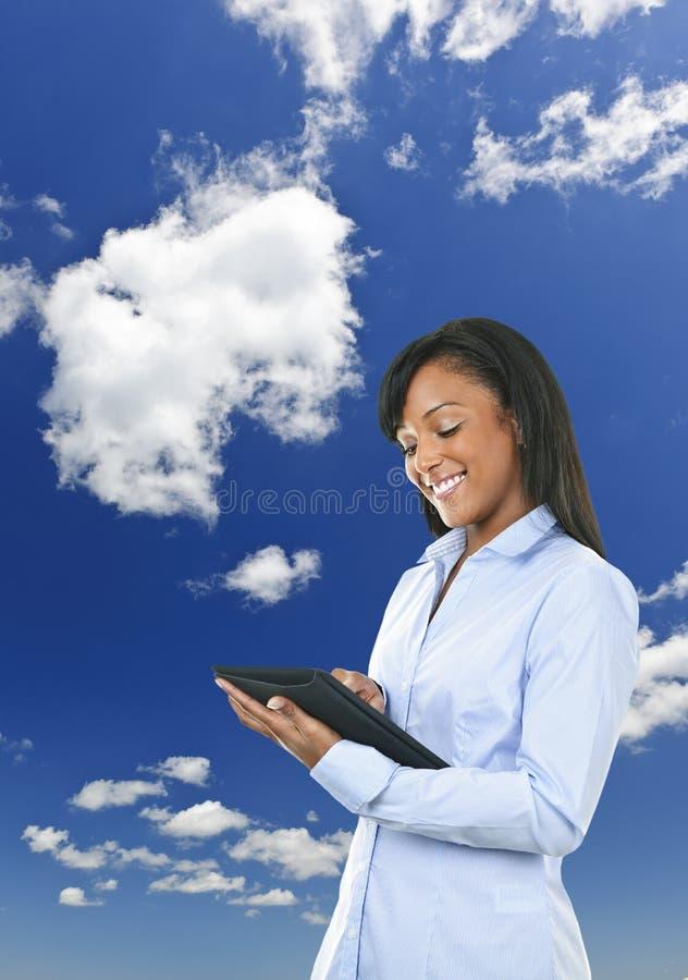 Gelukkige vrouw met tabletcomputer en wolken stock afbeelding