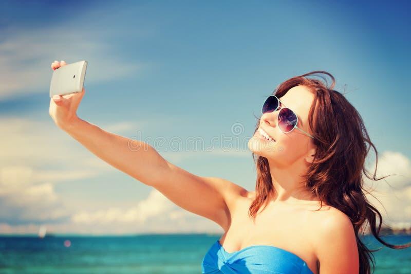 Gelukkige vrouw met telefoon op het strand stock afbeelding