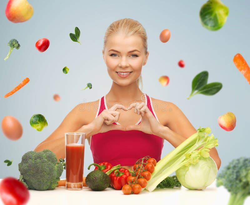 Gelukkige vrouw met vegetarisch voedsel die hart tonen stock fotografie