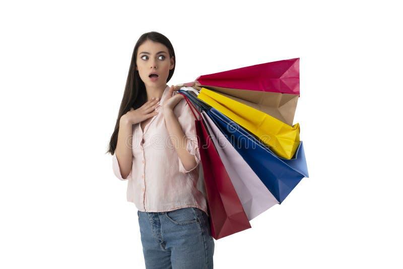 Gelukkige vrouw met verraste uitdrukking en het winkelen zakken Ge?soleerdj op witte achtergrond stock foto