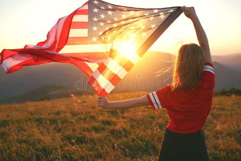 Gelukkige vrouw met vlag van Verenigde Staten die van de zonsondergang op Na genieten royalty-vrije stock foto's