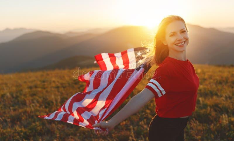 Gelukkige vrouw met vlag van Verenigde Staten die van de zonsondergang op Na genieten stock afbeelding