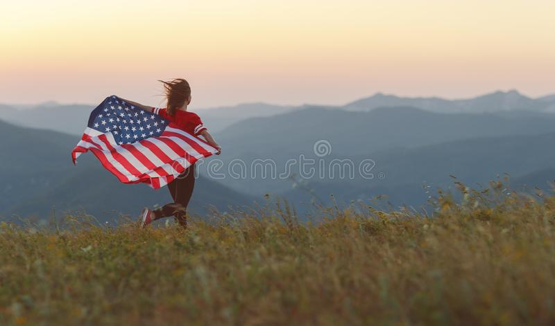 Gelukkige vrouw met vlag van Verenigde Staten die van de zonsondergang op Na genieten stock afbeeldingen