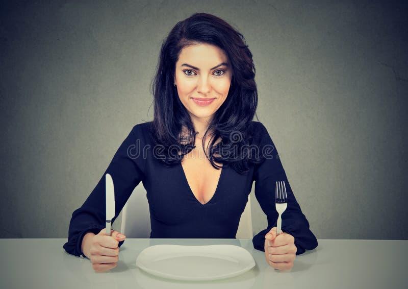 Gelukkige vrouw met vork en messenzitting bij lijst met lege plaat stock foto's