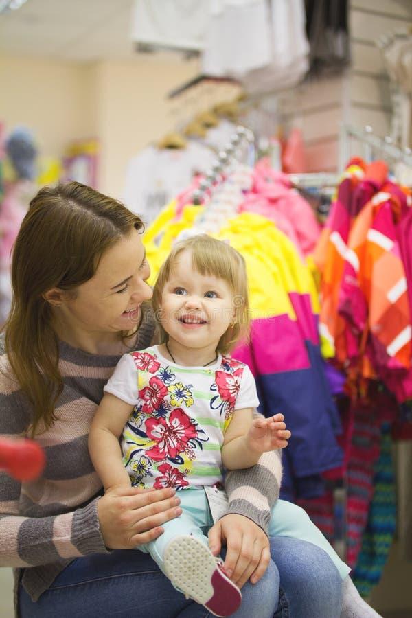 Download Gelukkige Vrouw Met Weinig Dochter Bij Kledingstuksupermarkt Stock Foto - Afbeelding bestaande uit meisje, aankoop: 114225466