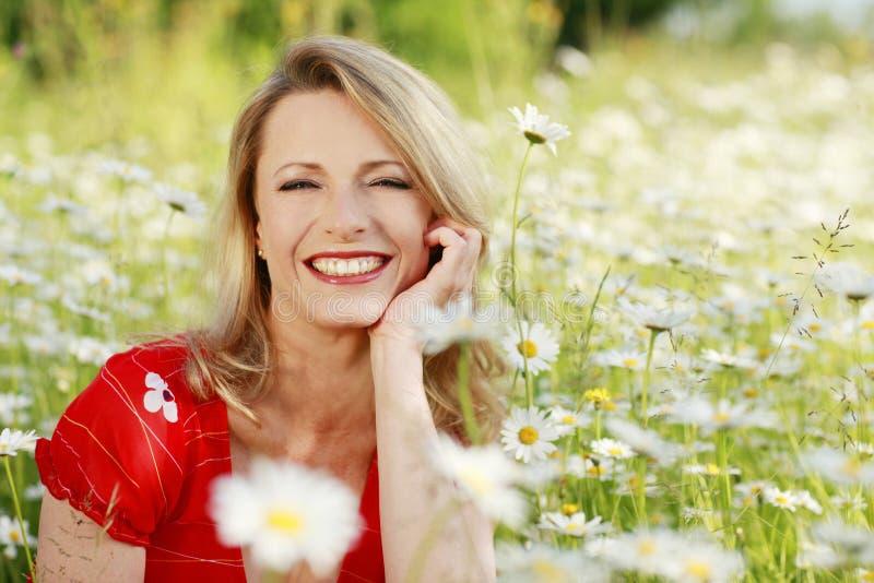 Gelukkige vrouw op bloemgebied stock foto
