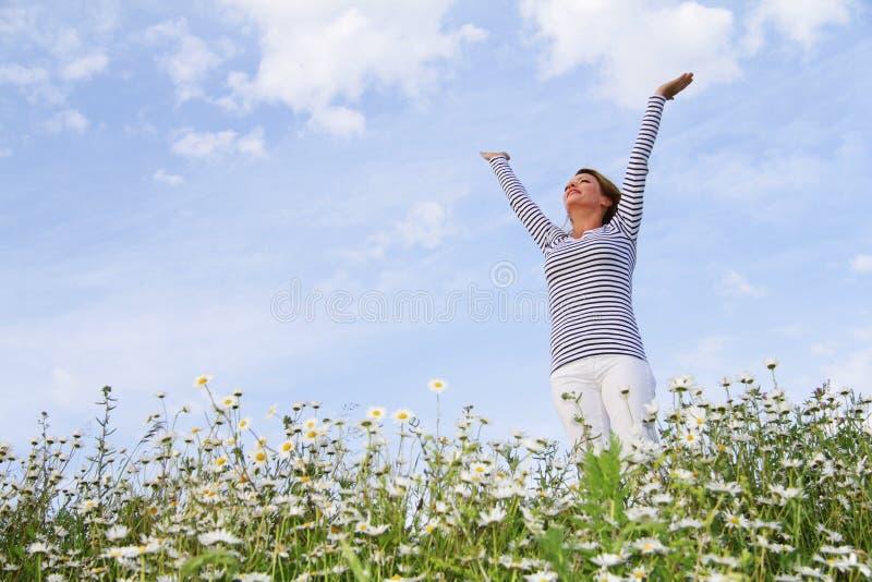 Gelukkige vrouw op bloemgebied stock afbeeldingen