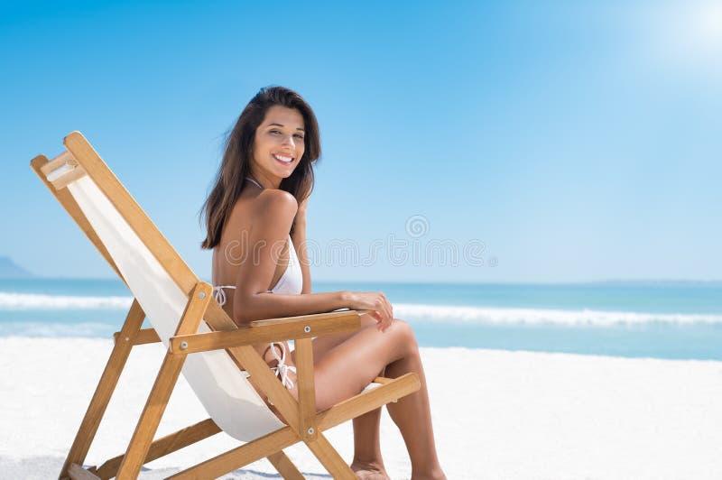 Gelukkige vrouw op deckchair bij strand stock foto's