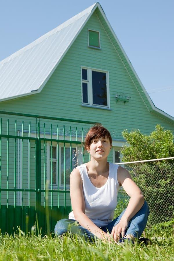 Gelukkige vrouw op gazon voor huis royalty-vrije stock afbeeldingen
