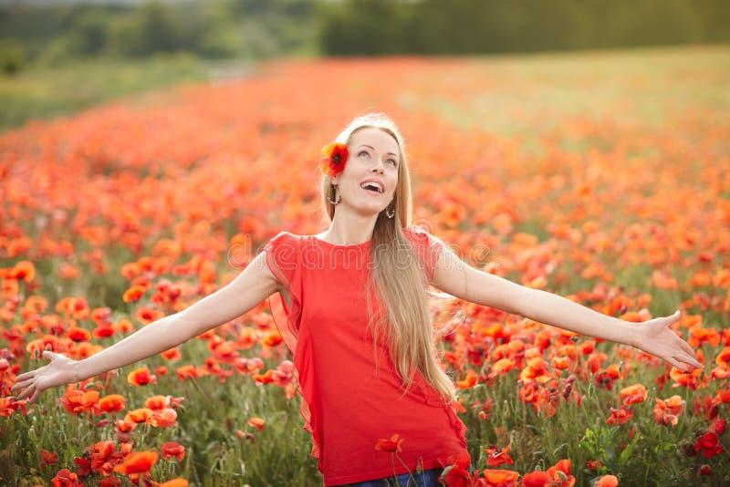 Gelukkige vrouw op het gebied van de papaverbloem stock afbeelding