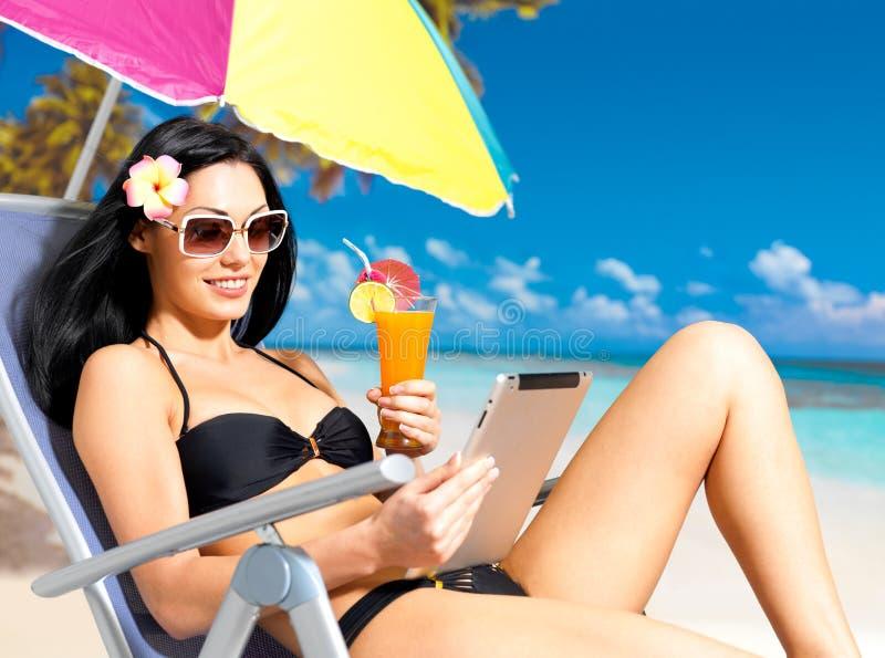 Gelukkige vrouw op het strand met ipad stock afbeelding