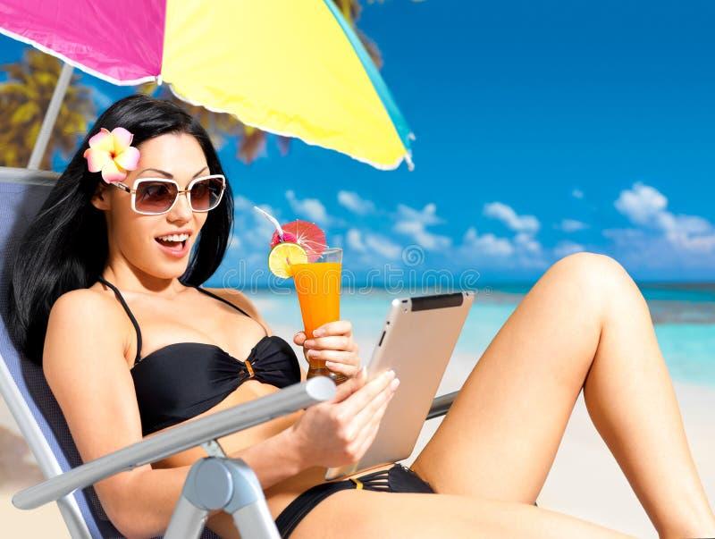 Gelukkige vrouw op het strand met ipad royalty-vrije stock afbeelding