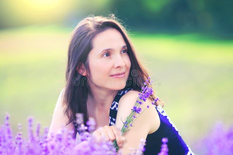 Gelukkige vrouw op lavendelachtergrond Mooi meisje in weide fie royalty-vrije stock afbeeldingen