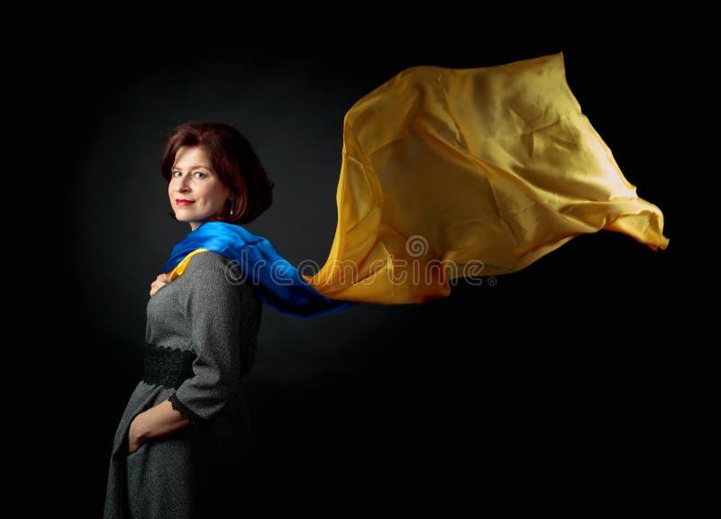 Gelukkige vrouw op middelbare leeftijd in een grijze kleding met een blauwe en gele sjaal royalty-vrije stock foto's