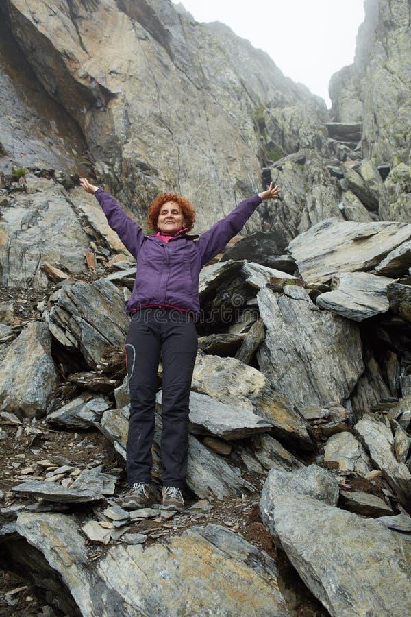 Gelukkige vrouw op rotsachtige bergen royalty-vrije stock afbeelding