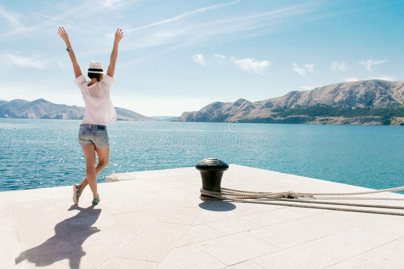 Gelukkige vrouw op vakantie die zich door het overzees bevinden Opgeheven wapens Het onbezorgde jonge wijfje geniet van vakantie royalty-vrije stock foto's