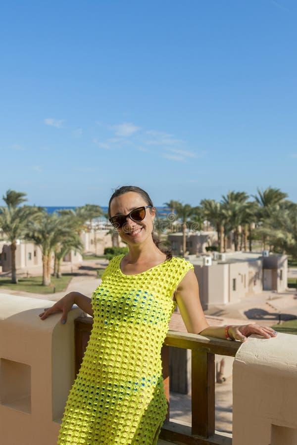 Gelukkige vrouw op vakantie tegen de achtergrond van het hotel Concept overzeese rust verticale foto royalty-vrije stock afbeeldingen