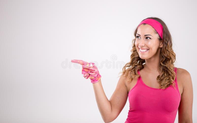 Gelukkige vrouw in schoonmakende uitrustingsholding die op iets richten royalty-vrije stock afbeeldingen