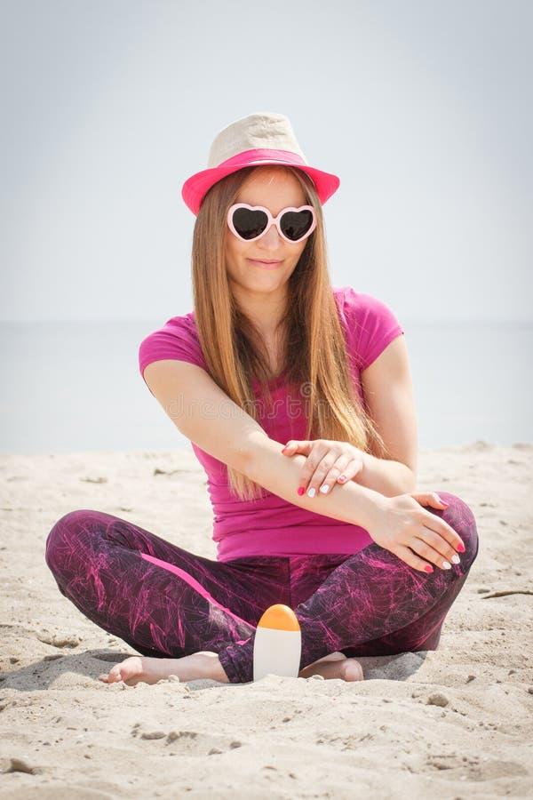 Gelukkige vrouw in strohoed en zonnebril die zonlotion, concept gebruiken zonbescherming op strand stock fotografie