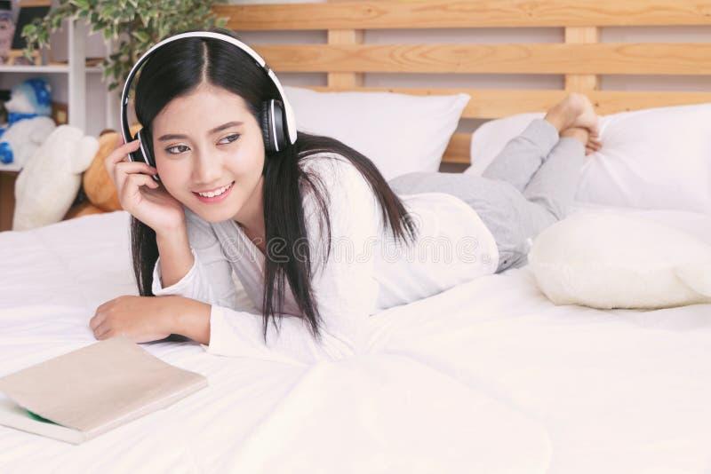 Gelukkige vrouw of tiener die in hoofdtelefoons aan muziek luisteren voor stock foto