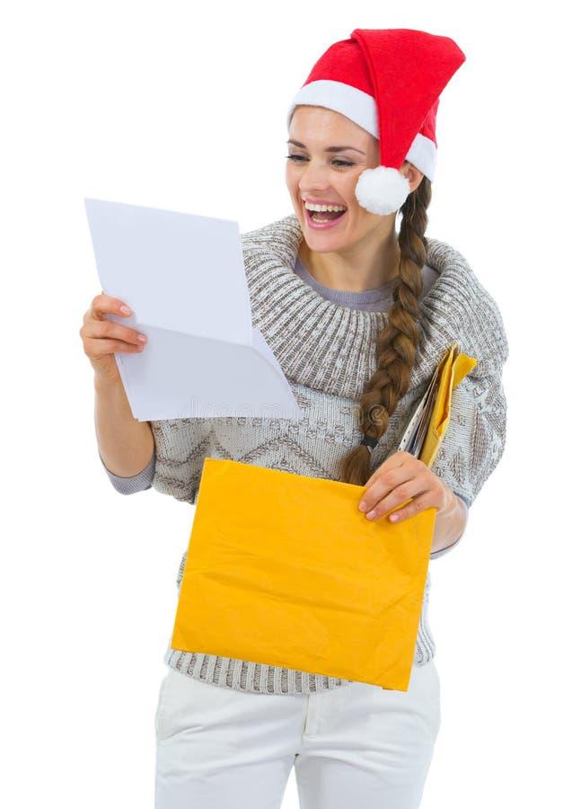 Gelukkige vrouw in van de de hoedenlezing van de Kerstman de brief van Kerstmis stock foto's