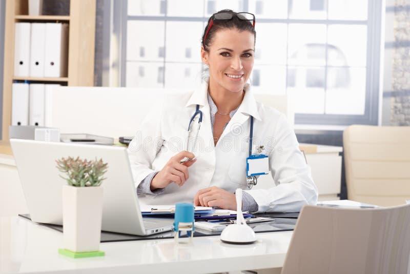 Gelukkige vrouwelijke artsenzitting bij medisch bureau stock foto