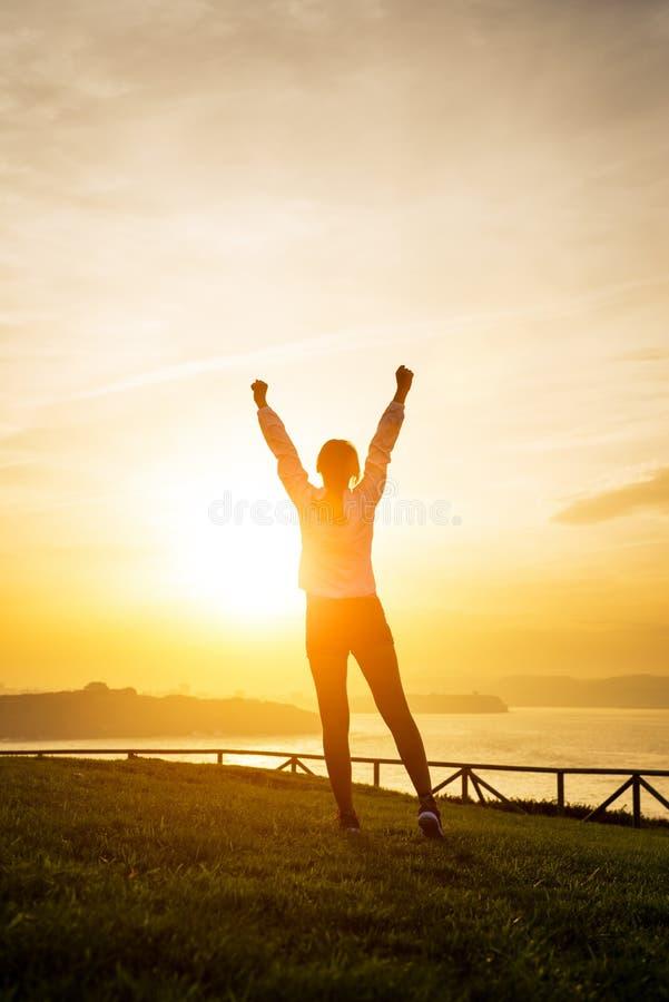 Gelukkige vrouwelijke atleet die wapens naar de zon opheffen stock afbeelding