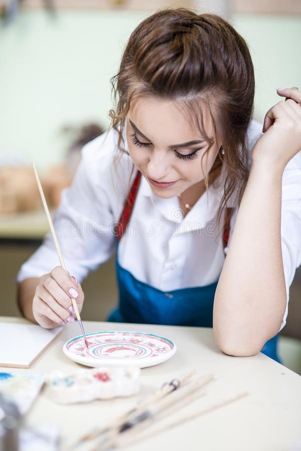 Gelukkige Vrouwelijke Ceramist die Penseel voor Verglazing en het Schilderen gebruiken royalty-vrije stock afbeelding
