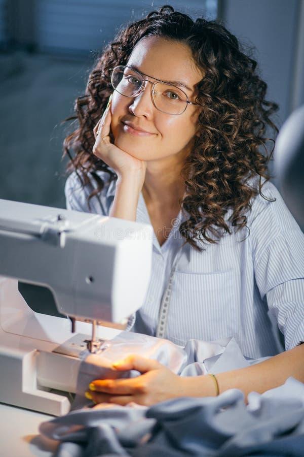 Gelukkige vrouwelijke kleermaker het besteden vrije tijd voor naaimachine stock foto