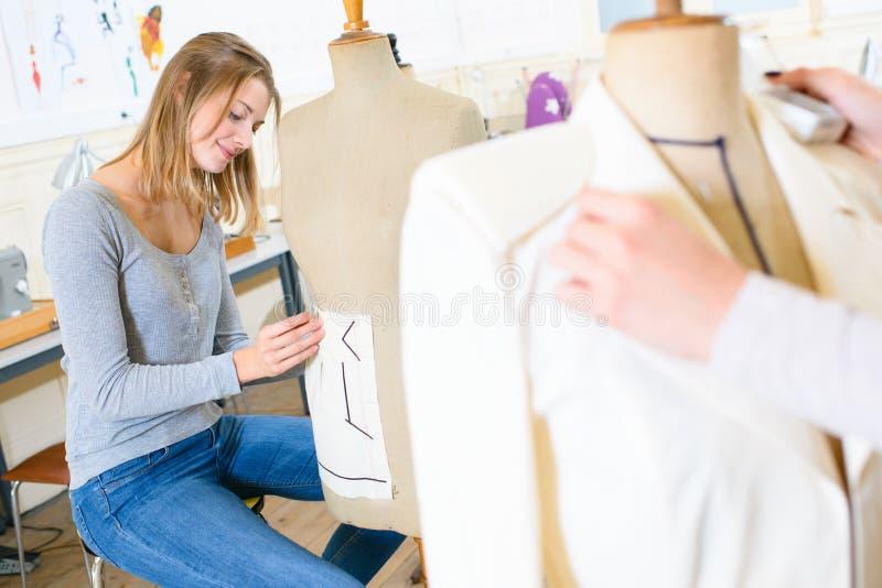 Gelukkige vrouwelijke kleermaker met kleermakersmodel stock foto