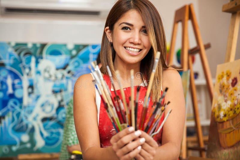 Gelukkige vrouwelijke kunstenaar op het werk stock fotografie