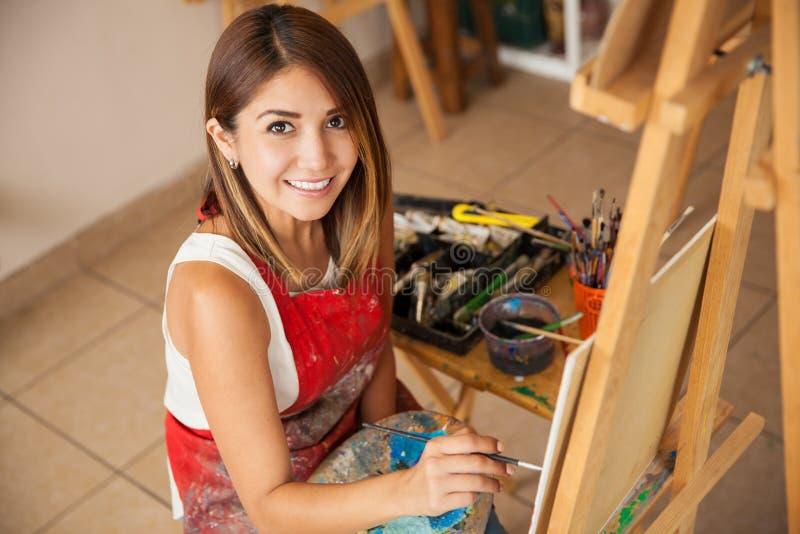 Gelukkige vrouwelijke kunstenaar op het werk stock foto