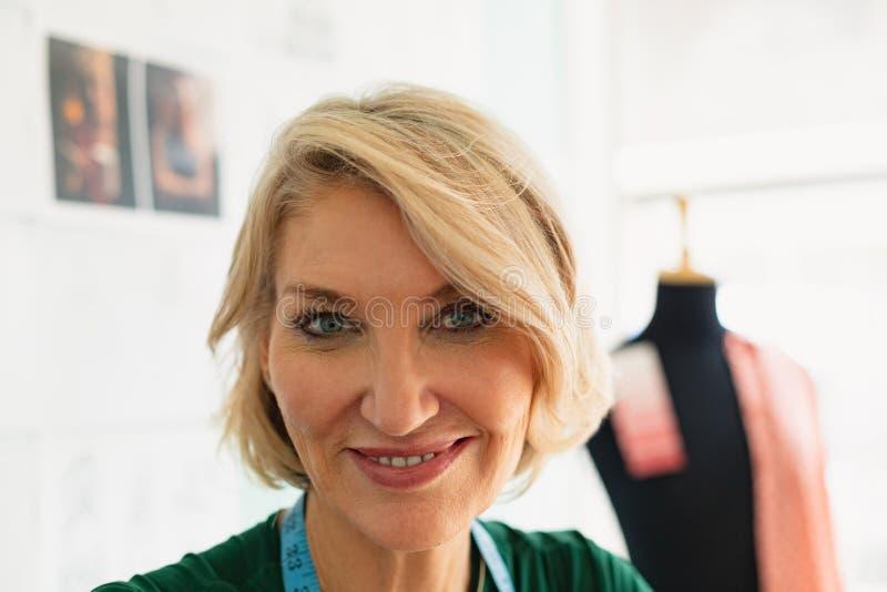 Gelukkige vrouwelijke manierontwerper die in de ontwerpstudio glimlachen royalty-vrije stock foto