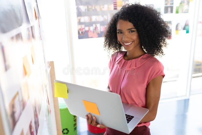 Gelukkige vrouwelijke manierontwerper die laptop in ontwerpstudio met behulp van royalty-vrije stock fotografie