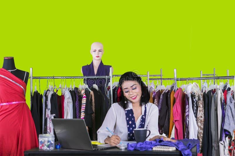 Gelukkige vrouwelijke naaister die nieuwe kleding trekken royalty-vrije stock foto