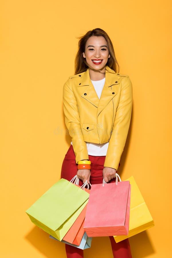 gelukkige vrouwelijke shopaholic status met document zakken op geel royalty-vrije stock afbeeldingen