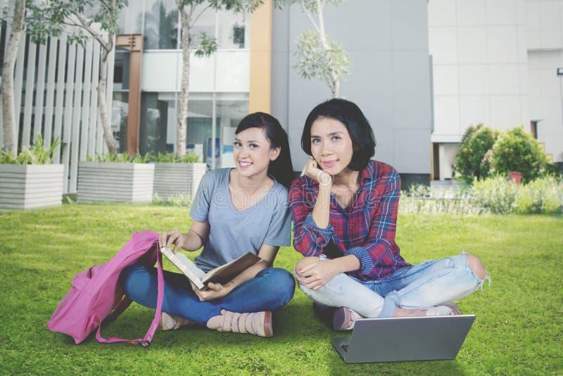 Gelukkige vrouwelijke studenten die in het park bestuderen royalty-vrije stock afbeeldingen