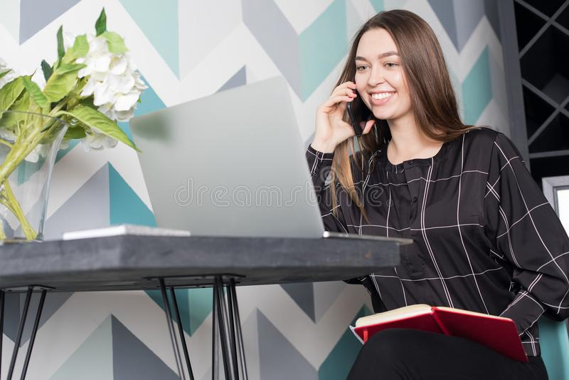 Gelukkige vrouwelijke universitaire student die online via laptop computer leren en op cellphone spreken stock foto