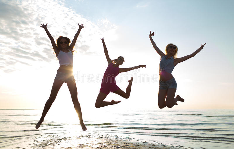 Gelukkige vrouwelijke vrienden die en op strand dansen springen royalty-vrije stock afbeelding