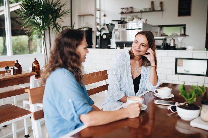 Gelukkige vrouwelijke vrienden die in koffie babbelen Twee mooie jonge vrouwen die en koffie drinken roddelen stock foto's