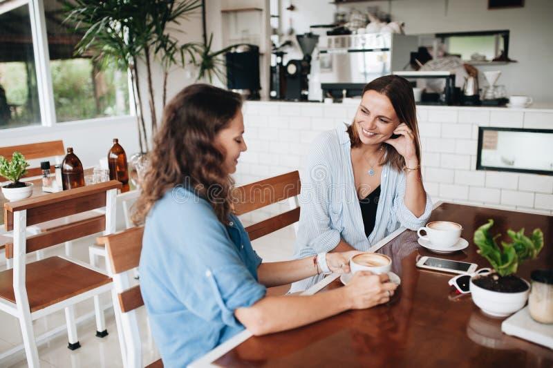 Gelukkige vrouwelijke vrienden die in koffie babbelen Twee mooie jonge vrouwen die en koffie drinken roddelen royalty-vrije stock foto's