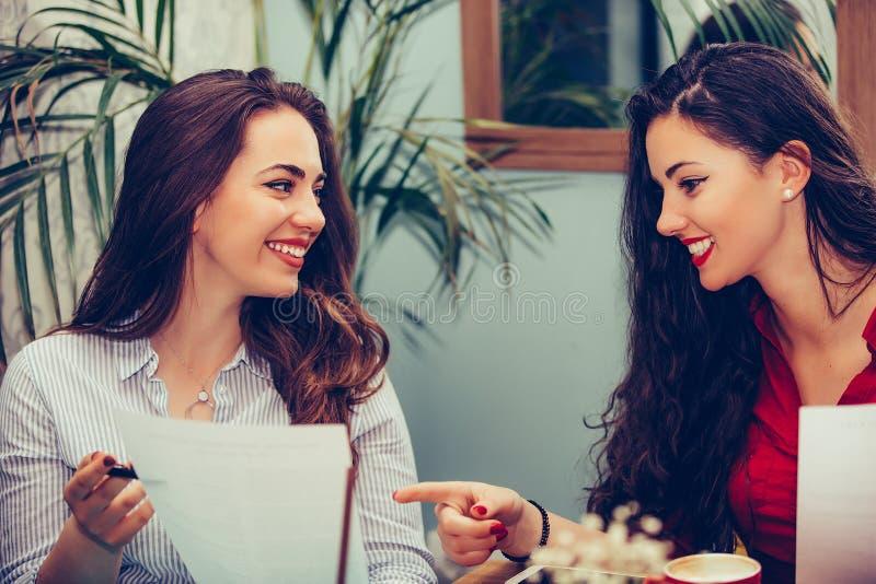 Gelukkige vrouwelijke vrienden, studenten die document lezen samen en richten waar te een contract te ondertekenen stock afbeeldingen