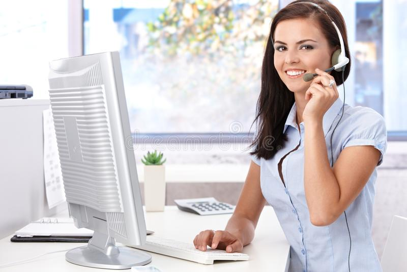 Gelukkige vrouwelijke zitting bij bureau in helder bureau stock afbeelding