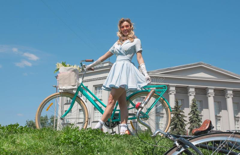 Gelukkige vrouwen in de zomerstemming klaar voor het cirkelen met uitstekende fiets voorbij Nationaal Museum van de Geschiedenis  stock foto