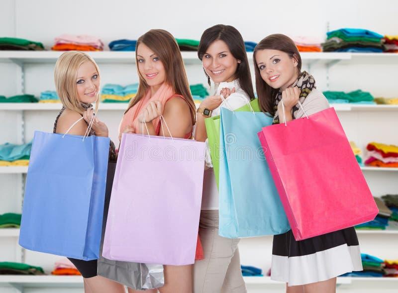 Gelukkige Vrouwen die het Winkelen Zakken in Opslag dragen stock afbeeldingen