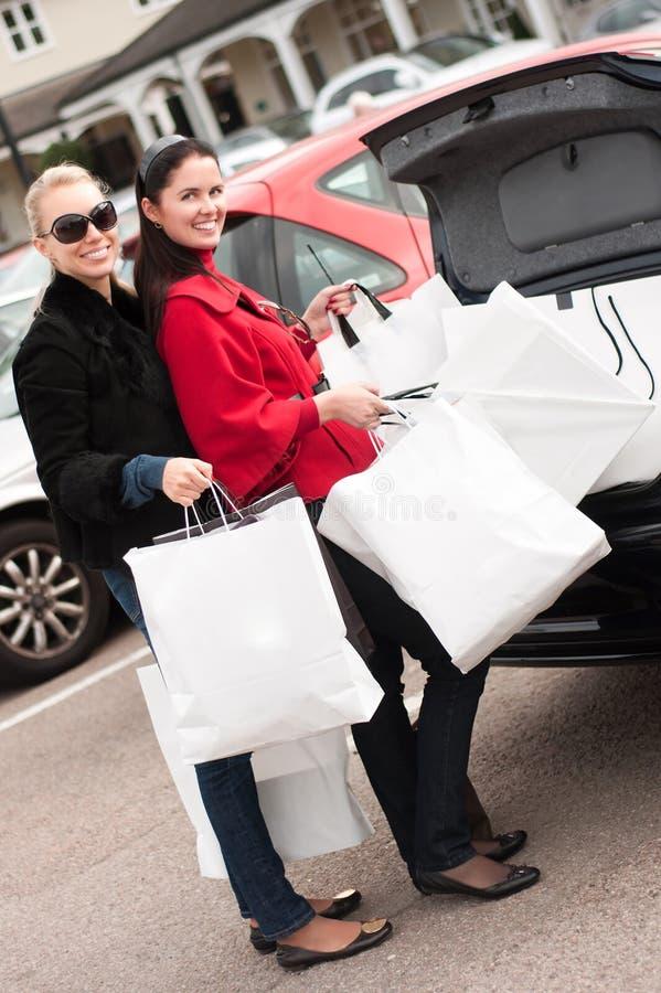 Gelukkige vrouwen die het winkelen zakken zetten in de autoboomstam stock fotografie